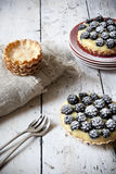 Two homemade blackberries tart with pastry cream on wooden table with cloth, fork and little plate Royalty Free Stock Photo