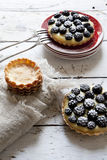 Two homemade blackberries tart with pastry cream on wooden table with cloth, fork and little plate Royalty Free Stock Image