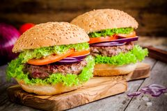 Two homemade burgers with fresh organic lettuce, tomato and red onion Royalty Free Stock Image