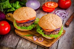 Two homemade burgers with fresh organic vegetables on a rustic background Royalty Free Stock Photos