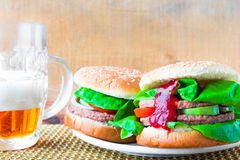Two homemade grilled hamburger with cold beer Stock Photo