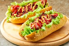 Two homemade hot dogs with lettuce, bacon and onion toppings. On round wooden board royalty free stock image