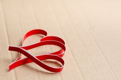 Two homemade paper red hearts on a beige cardboard background. stock photo