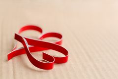 Two homemade paper red hearts on a cardboard background close up, the symbol of Valentine`s Day.  royalty free stock photo