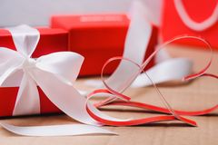 Two homemade paper red hearts and red gift boxes tied with white ribbons. Valentine`s day and love symbol stock photography