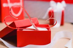 Two homemade paper red hearts and red gift boxes tied with white ribbons. Valentine`s day and love symbol.  royalty free stock photos