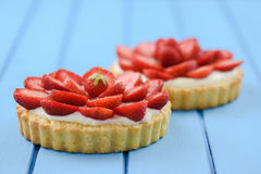 Two homemade tarts with fresh sweet strawberries and mascarpone. Cheese on blue table with space stock photography