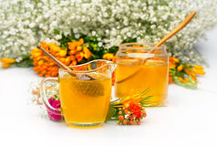Two Honey jars with stick and flowers near Stock Photo