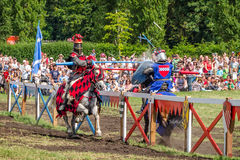 Two horsemen have heavy spears contact at jousting tournament Stock Image