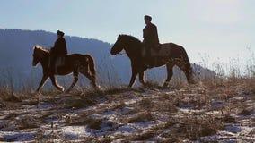 Two horsemen. Two horsemen riding on horses through mountainous terrain stock footage