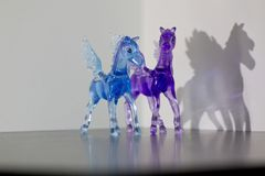 Two glass winged pegasus. Two horses with wings against white background Stock Photography