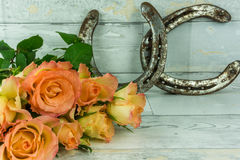 Two horseshoes with a bouquet of roses. On a rustic white wooden background Stock Images