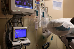 Two hospital monitors by a patient& x27;s bed. Two hospital monitors hooked up to a patient in a recovery room bed in a hospital.  Patient is barely visible Stock Photography