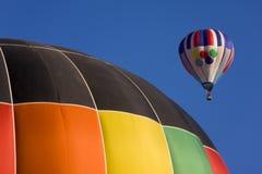 Two hot air balloons. Multi color hot air balloon flies over second balloon Royalty Free Stock Photos