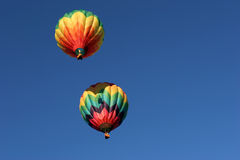 Two hot air balloons. Two colorful hot air balloons, top one casting its shadow of the basket as it fires its burners to climb Stock Images