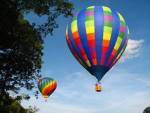 Two Hot Air Balloons. Two rainbow colored hot air balloons flying over the trees Royalty Free Stock Image