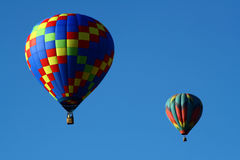 Two Hot Air Balloons. Two colorful hot air balloons soar in a beautiful blue sky Stock Photography