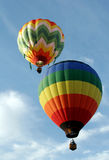 Two Hot Air Balloons. Flying through the sky royalty free stock images