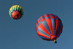 Two hot air balloons from below. Two colorful hot air balloons ascending into a deep blue sky Royalty Free Stock Photos