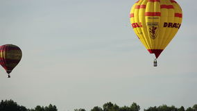 Two hot air balloons flying in the sky over the forest. Multicolored hot air balloons flying in the sky over the forest, fast shooting, hot air balloons fly into stock footage