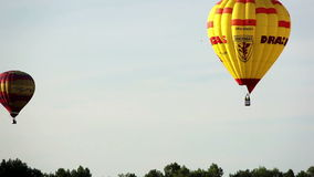 Two hot air balloons flying in the sky over the forest. Multicolored hot air balloons flying in the sky over the forest, fast shooting, hot air balloons fly into stock video footage