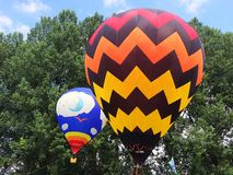 Two hot air balloons in front of trees in the day light. Picture of 2 balloons , filled with hot stock photo