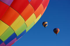 Two hot air balloons taking off. A great morning with colorful hot air balloons taking off into a clear blue sky with a great balloon in the foreground giving Stock Photos