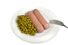 Two hot boiled sausages with canned green peas on a white plate are served for dinner Stock Image