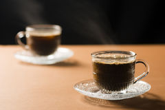 Two hot coffees. Two cup of hot coffees on table on black background Royalty Free Stock Images