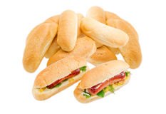 Two hot dog and pile of a buns with sesame. Two hot dog with grilled frankfurter, cheese and mayonnaise in bun with sesame seeds on a background of pile of the stock photos