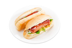 Two hot dog on a white dish. Two hot dog with grilled frankfurter, cheese and mayonnaise in bun with sesame seeds on a white dish on a light background royalty free stock images