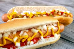 Two hot dogs. Closeup with ketchup , yellow mustard and onion on gray wooden surface Royalty Free Stock Photo