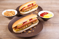 Two hot dogs with gherkin and onions Stock Images