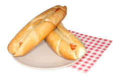 Two hot dogs with mustard on brown plate. And napkin, isolated Royalty Free Stock Photography