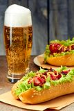 Two hot dogs with toppings and glass of beer. Two hot dogs with bacon and onion topings, glass of beer on stone table royalty free stock image