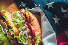Two hot dogs on a wooden Board, glasses with Cola and American flag Royalty Free Stock Photos