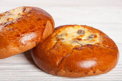 Two hot fresh buns. Two fresh homemade buns with cottage cheese and raisins on a wooden background Royalty Free Stock Image
