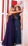 Two hot girls in evening dresses in vintage room Royalty Free Stock Image
