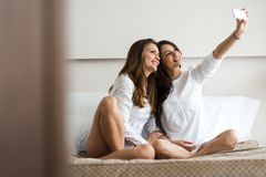 Two hot girls lying  on a bed taking a photo of themselves with. Two beautiful women lying  on a bed taking a photo of themselves with a phone in a luxorious Stock Image