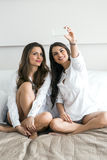 Two hot girls lying  on a bed taking a photo of themselves with. Two beautiful women lying  on a bed taking a photo of themselves with a phone in a luxorious Royalty Free Stock Photo
