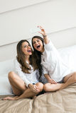 Two hot girls lying  on a bed taking a photo of themselves with. Two beautiful women lying  on a bed taking a photo of themselves with a phone in a luxorious Stock Photography