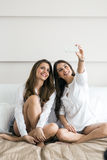 Two hot girls lying  on a bed taking a photo of themselves with. Two beautiful women lying  on a bed taking a photo of themselves with a phone in a luxorious Royalty Free Stock Image