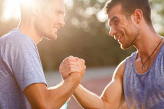 Two hot men shake each others hands on summer day. Two hot athletic men shake each others hands on summer day Royalty Free Stock Photography