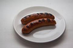 Two hot sausages on plate Royalty Free Stock Photos