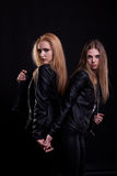 Two hot sexy women in leather jackets posing on black background. In studio photo. Sexuality and sensuality. Beauty and fashion. Passion and erotica Stock Photo
