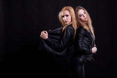 Two hot sexy women in leather jackets posing on black background. In studio photo. Sexuality and sensuality. Beauty and fashion. Passion and erotica Stock Photography