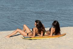 Two hot slim dark-haired girls in swimsuits lay near the yellow surfboard on the sandy beach near the sea on a sunny day.  stock photos