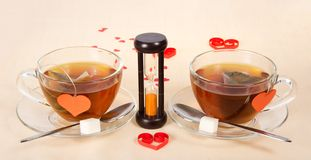 Two hot teas and hourglasses Stock Image
