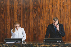 Two hotel employees doing their job Royalty Free Stock Photos