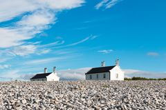 Two houses with chimneys. Two houses on a hill with blue sky and white clouds near Puffin island in Wales royalty free stock photo